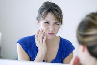 woman holding jaw from pain | Dentist Barrie ON