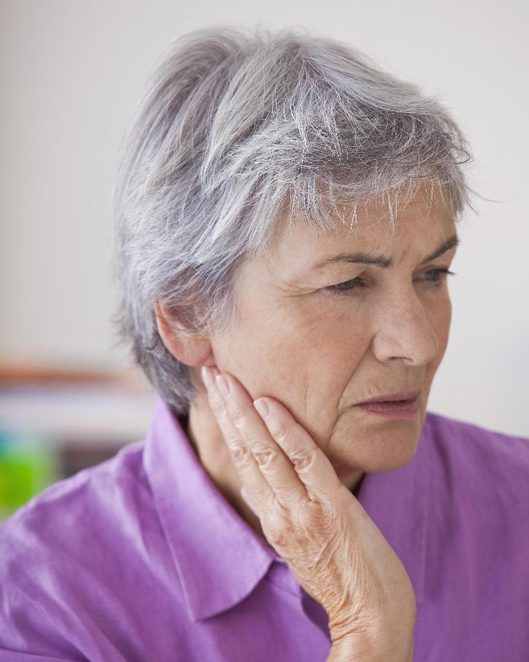 Woman holding jaw in pain| Dentist Barrie ON