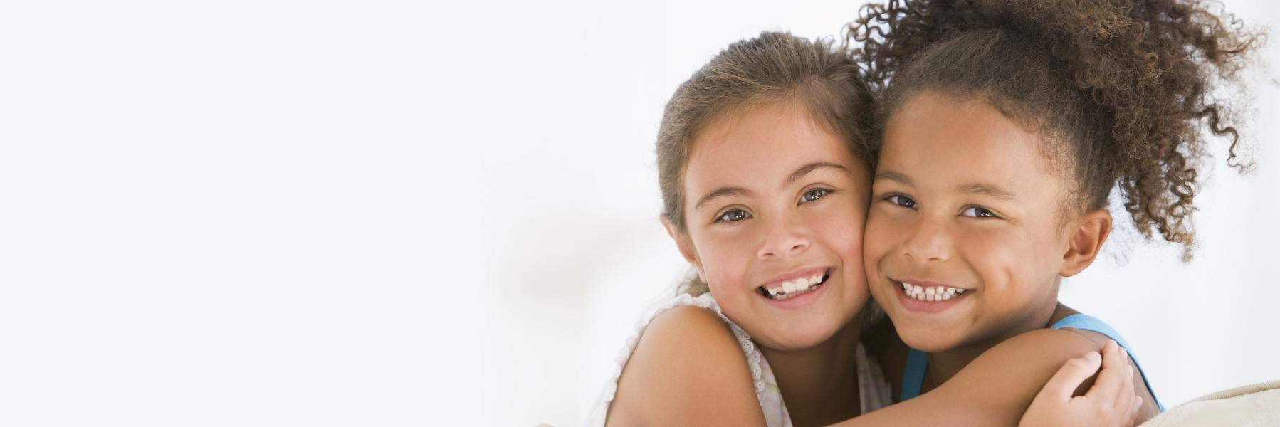 Two young girls hugging | Dentist Barrie ON